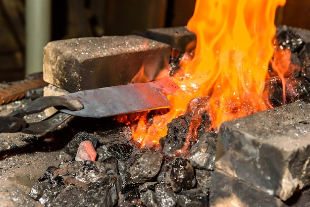 Warming up the metal in heat. the forge.