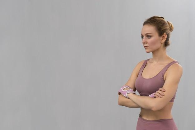 Разминка, растяжка, скрестив руки, молодая женщина упражнениями