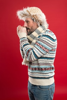 ウォーミングアップ。冬のファッション。ニットアクセサリー。寒い冬の条件。帽子とスカーフの赤い背景を身に着けているハンサムなひげを生やした男。フェイクファー。メンズウェアのコンセプト。ファッションコレクション。ファッション服。