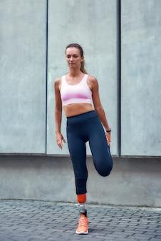 Разогревающая молодая и красивая женщина с протезом ноги в спортивной одежде растягивается перед