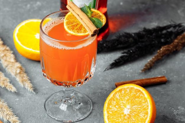 Согревающий зимний коктейль с аперолом. горячий апероль. коктейль на рождество. рождественский зимний коктейль с ананасовым соком aperol spritz martini и специями.