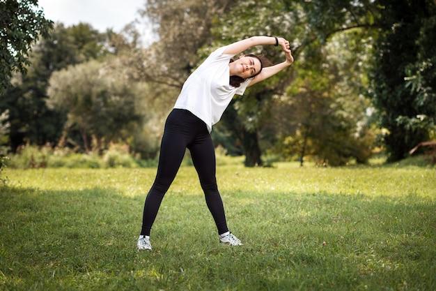 Разминка в парке. молодая здоровая кавказская женщина в спортивной одежде делает боковые наклоны. концепция спортивной тренировки
