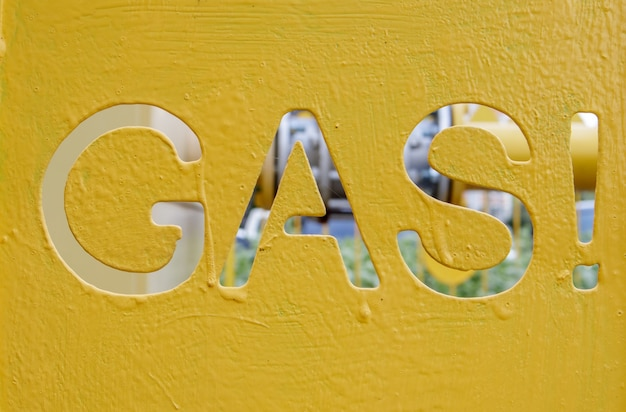 Warning on a metal cage with gas equipment for the public. attention gas pipe. the inscription in english gaz. a yellow warning sign for a medium pressure gas pipeline on a surface installation.