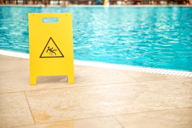 Warning plates wet floor beside the pool made of yellow plastic with copy space.