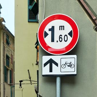 Warning road sign located forward of the narrow street in genoa city, italy