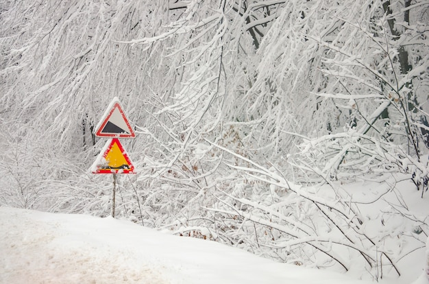 Warning road signs on the snowy frosted branches