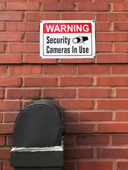 使用中の警告セキュリティカメラはレンガの壁にサインします