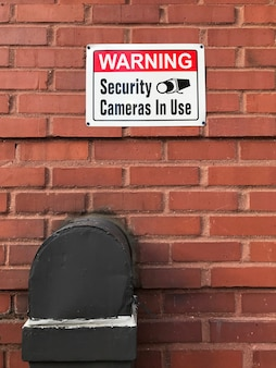 Warning security cameras in use sign on a brick wall