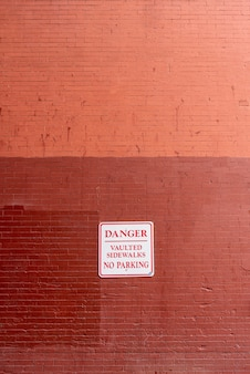Warning sign on brick wall front view
