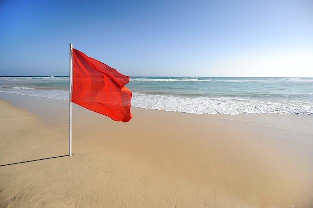 青い空とターコイズブルーの海と美しいビーチで赤い旗の警告サイン