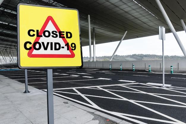 Предупреждающий знак с текстом закрыто covid-19 на пустой стоянке аэропорта или железнодорожного вокзала. крионавирусная кризисная концепция
