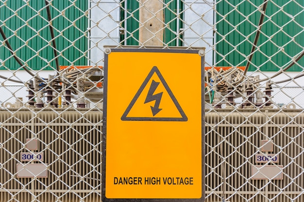 Warning sign at a work site with transformers high voltage in the background