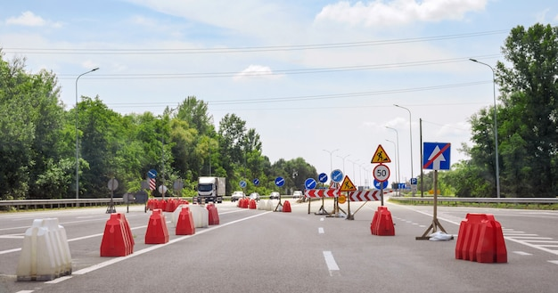 교통 방향을 보여주는 도로의 위험한 부분에 경고 표지판. 도로공사