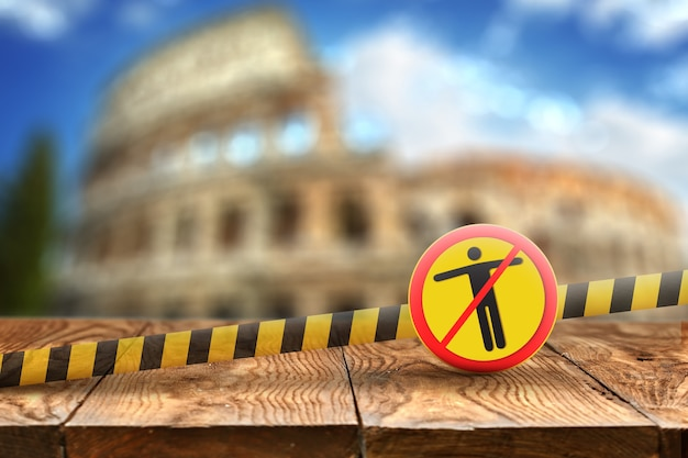 Warning yellow sign with crossed out man on a fencing ribbon on a  of wooden table and blurred colosseum in rome, italy. coronavirus, covid 19 pandemic, quarantine concept.
