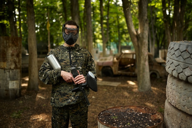 Warrior in camouflage and mask holds paintball gun. extreme sport with pneumatic weapon and paint bullets or markers, military game outdoors