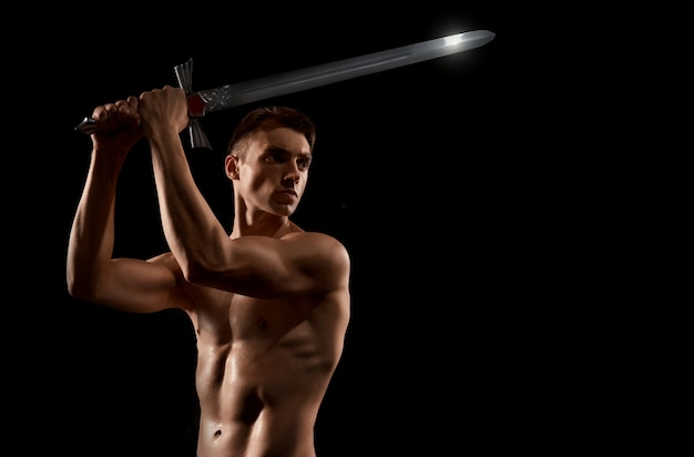 Warrior fight with sword isolated on black.