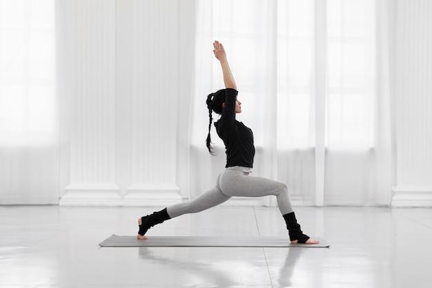 Warrior i pose beautiful young asian woman practicing yoga pose on gray mat at yoga studio