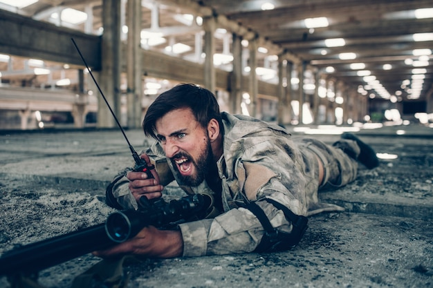 Warrior is screaming in portable radio. he is lying on the ground with big rifle. guy has protection on his elbows. also he is holding finger on a trigger.