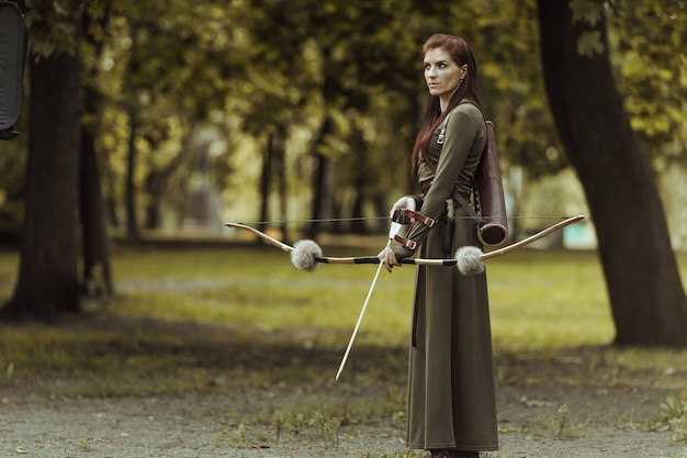 Warrior medieval woman with bow hunting in green forest