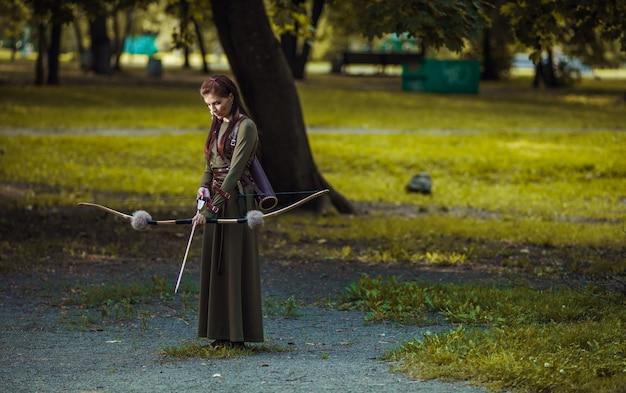 Средневековая женщина воин с луком охота в зеленом лесу