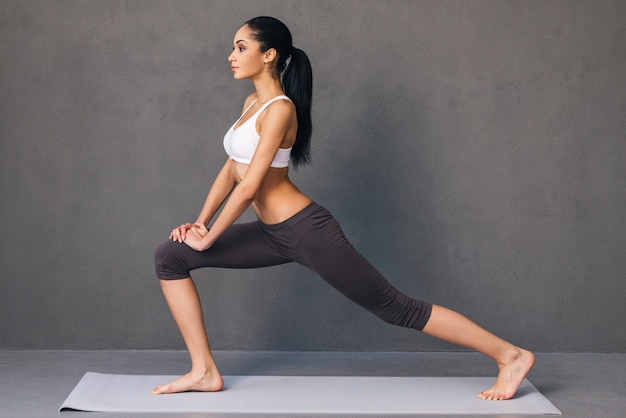 戦士。灰色の背景にエクササイズマットでヨガを練習するスポーツウェアの美しい若いアフリカの女性の側面図