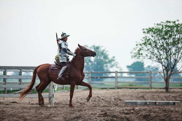 Warrior in traditional armor riding horse in farm