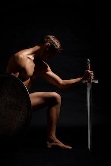 剣が膝の上に立っている戦士。