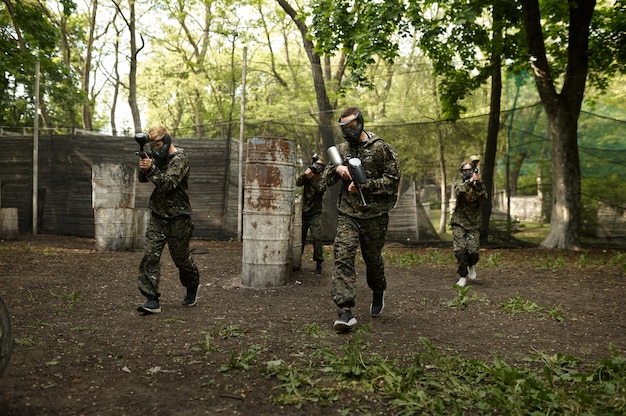 Warriors in camouflage and masks playing paintball. extreme sport with pneumatic weapon and paint bullets or markers, military team game outdoors, combat tactics