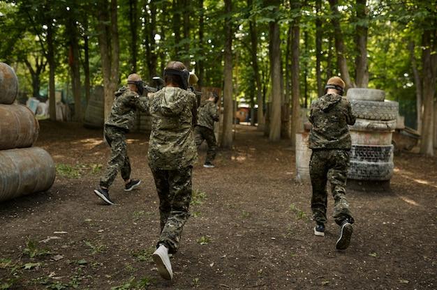 Воины в камуфляже и масках играют в пейнтбол