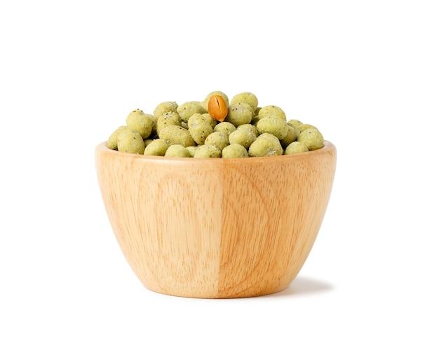 Хрустящие шарики закуски арахиса васаби в деревянной чашке изолированной на белом космосе.