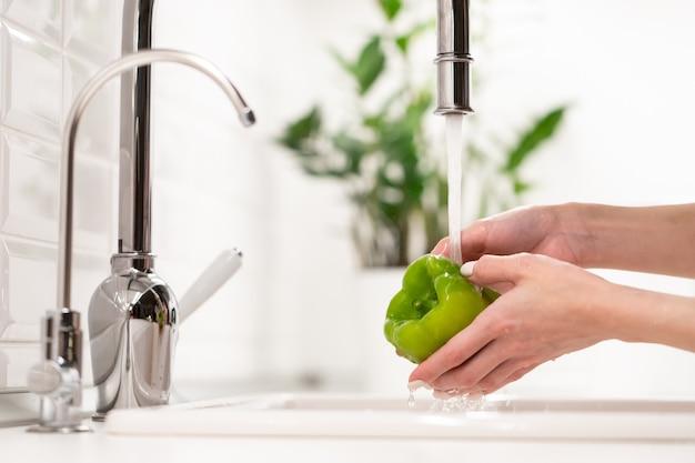 샐러드 위생 개념을 요리하기 전에 싱크대에 있는 물에 녹색 후추를 씻는 여성을 먹기 전에 씻으십시오