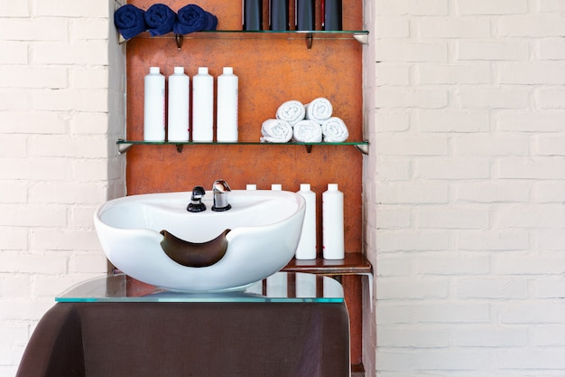 Wash sink for washing hair in beauty salon or barber shop, shampoos, towels. hairdresser stylist work space.