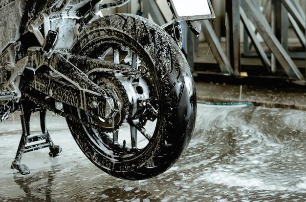 세차장에서 오토바이를 세차하십시오. 바퀴에 거품 세차