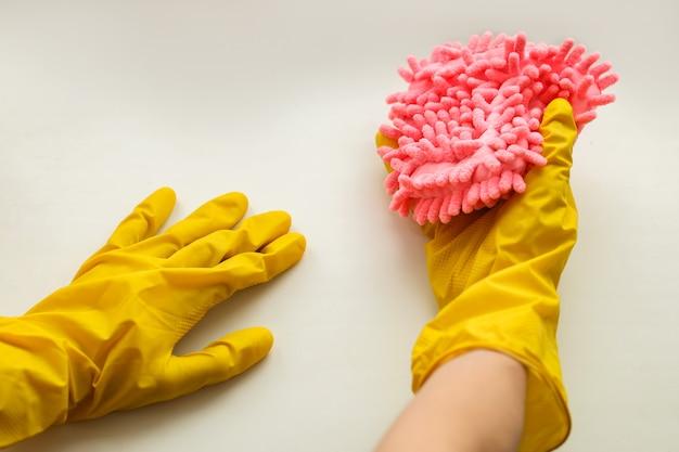 白いカウンタートップを黄色い手袋で洗ってください。ほこり、汚れ、バクテリアウイルスの洗浄、除去。クリーンな環境のコンセプト。高品質の写真