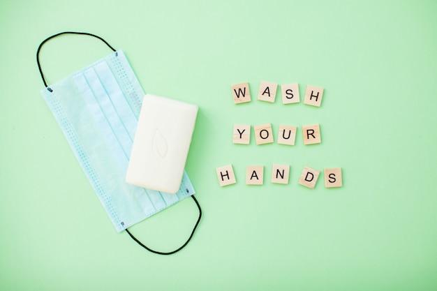 薄緑色の背景に手と石鹸と保護医療マスクを洗う