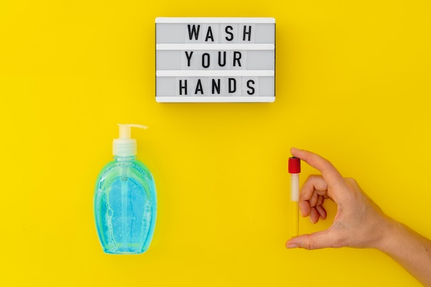 Мойте руки лайтбоксом с медицинской маской, светлым мылом и медицинскими перчатками. вид сверху на желтом фоне