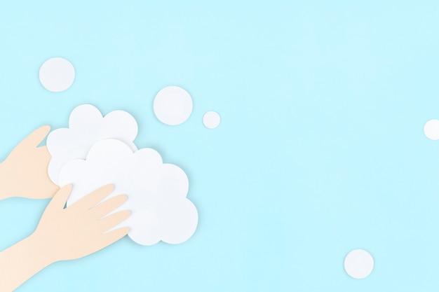 コロナウイルスパンデミックペーパークラフトの背景の間に石鹸で手を洗う