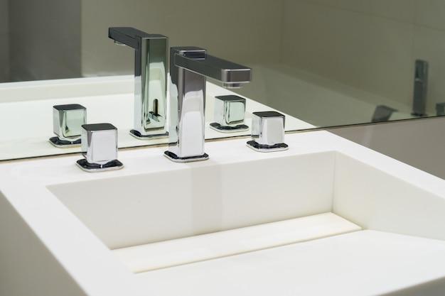 Умывальник и смесители в зеркале в ванной