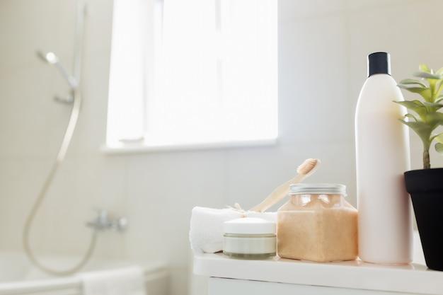 욕실 액세서리가있는 흰색 욕실의 세면대 및 샤워 시설. 호텔 청소 개념. 가정용 개념. 샴푸, 바디 스크럽, 크림, 칫솔, 수건. 창에서 빛.