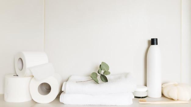 흰색 욕실의 세면대, 목욕 액세서리가 있는 선반. 호텔 청소 개념입니다. 가구 개념입니다. 수건, 샴푸병, 바디크림, 흰 화장지, 유칼립투스잎, 칫솔
