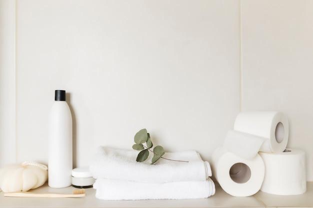 욕실 액세서리가있는 흰색 욕실의 세면대. 호텔 청소 개념. 가정용 개념. 수건, 샴푸, 크림, 화장지, 식물, 칫솔.
