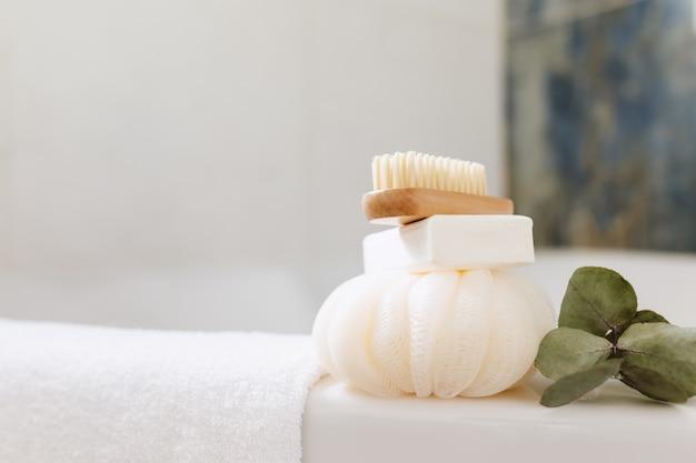 목욕 액세서리가 있는 흰색 욕실의 세면대. 호텔 청소 개념입니다. 가구 개념입니다. 수건, 비누, 발 브러시, 흰 수건, 녹색 잎이 있는 유칼립투스 가지. 세련된 욕실