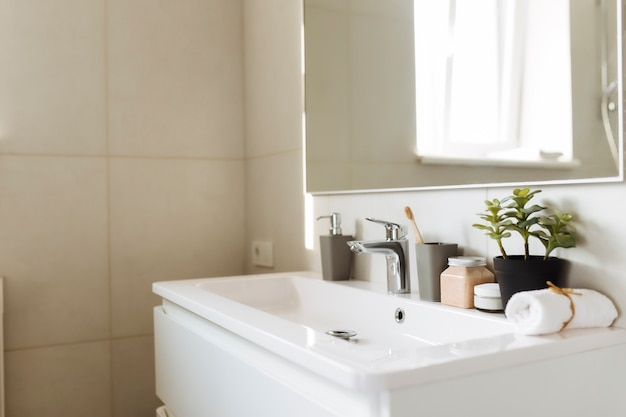 Умывальник в белой ванной с банными принадлежностями. концепция уборки отеля. концепция домашнего хозяйства. Premium Фотографии