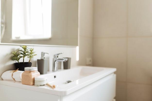 Умывальник в белой ванной с банными принадлежностями. концепция уборки отеля. концепция домашнего хозяйства.