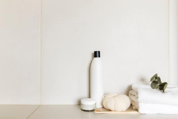 Умывальник в белой ванной с банными принадлежностями