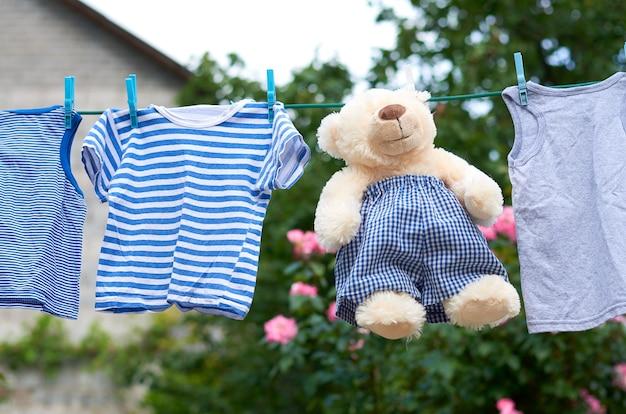 Постиранная детская одежда на веревке с прищепками и бежевый мишка