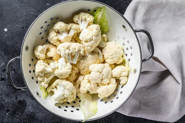 Washed fresh cauliflower cut into pieces in a colander