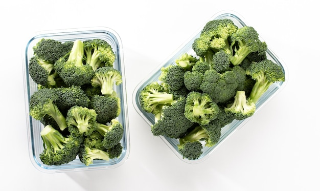Washed and sliced broccoli crown in glass container organic broccoli, cut up and ready to be used in cooking