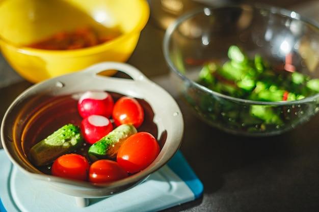 サラダを作るために台所のテーブルのザルで洗った野菜