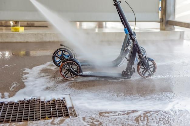 洗車場で汚れたスクーターを高圧水で洗う。スクーターのお手入れと清掃。